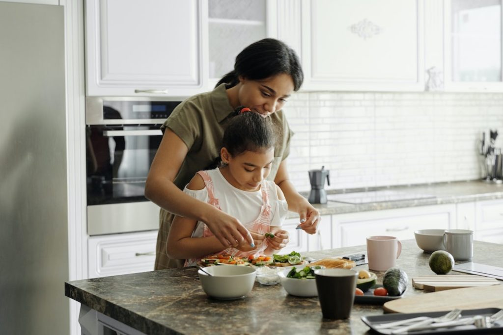 Mother and daughter preparing nutritious food to get rid of headaches through diet