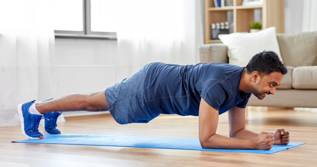 sport, fitness and healthy lifestyle concept - man doing plank exercise at home